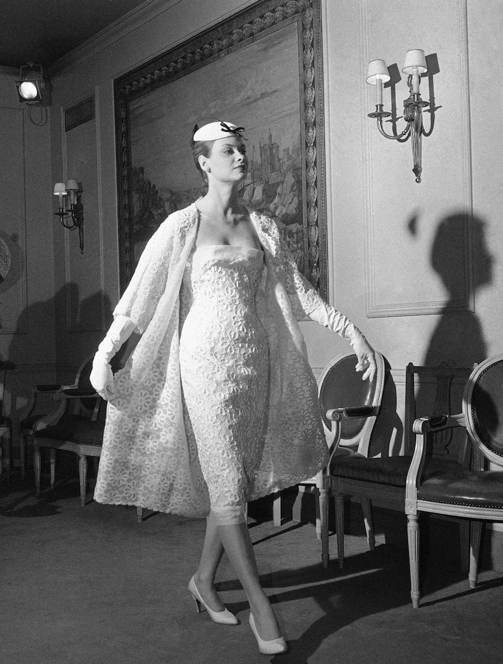 """This white lace short evening dress and matching coat was one of the late Christian Dior's creation designed before his death in fall in 1957. The evening dress was among those at the National press week showings in New York on Jan. 3, 1958 which featured fashions for spring, 1958. Dior called this collection, designed for the American market, The """"New Era"""". (AP Photo)"""