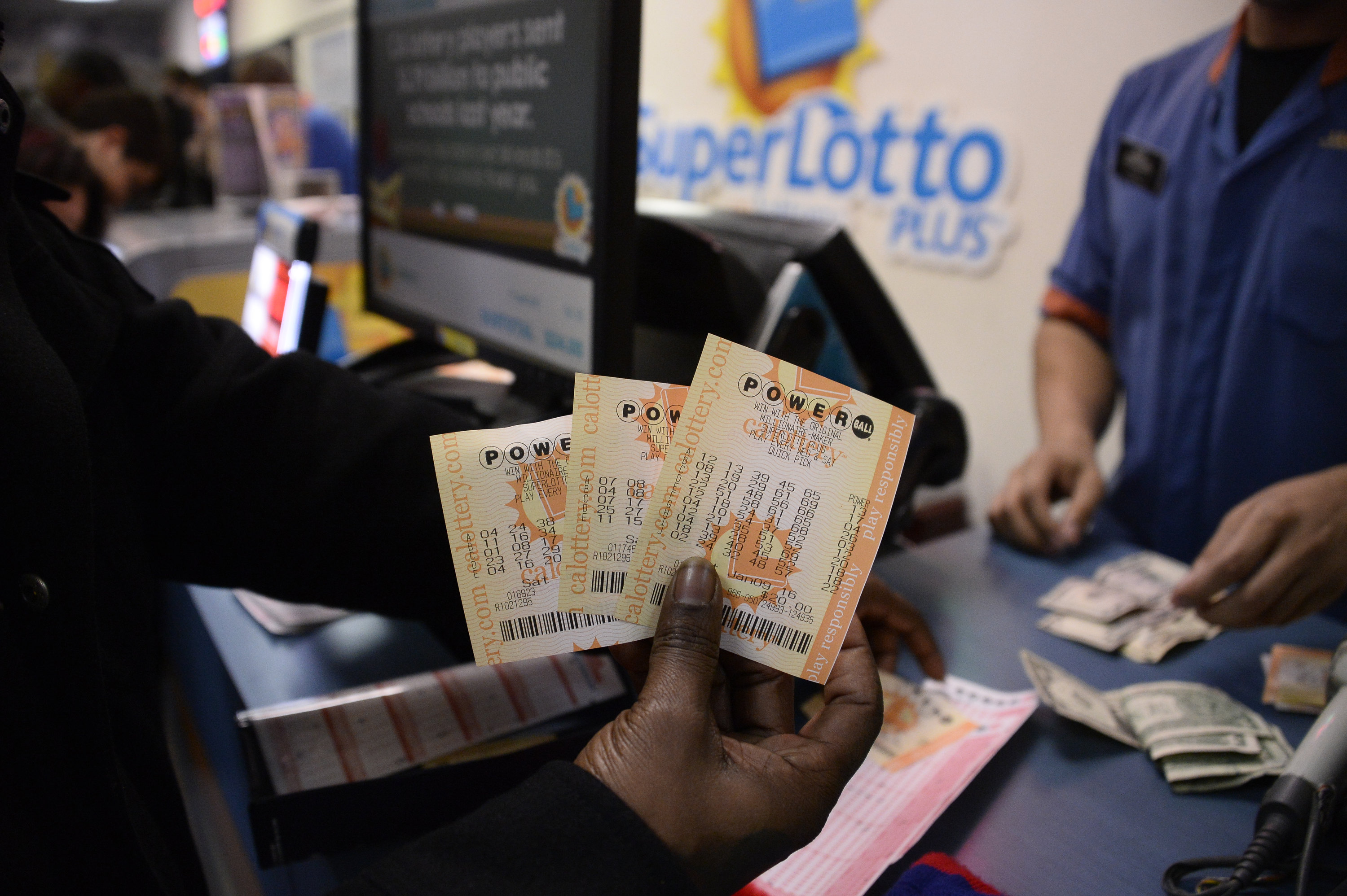 A customer shows their tickets for the Powerball lottery at the CA lotto store in San Bernardino County, California